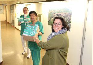 Der leitende Oberarzt Jiantao Peng (Mitte) überreicht Daniela Aevermann (vorne), Verwaltungsdirektorin, und dem Ärztlichen Direktor, Dr. Peter Ahrens, für die Aller-Weser-Klinik gGmbH gespendete Schutzmasken.