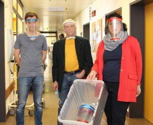 Günther und Nils Bohlmann übergeben Verwaltungsdirektorin Daniela Aevermann die mit dem 3D-Drucker selbst gefertigten Schutzschilde.